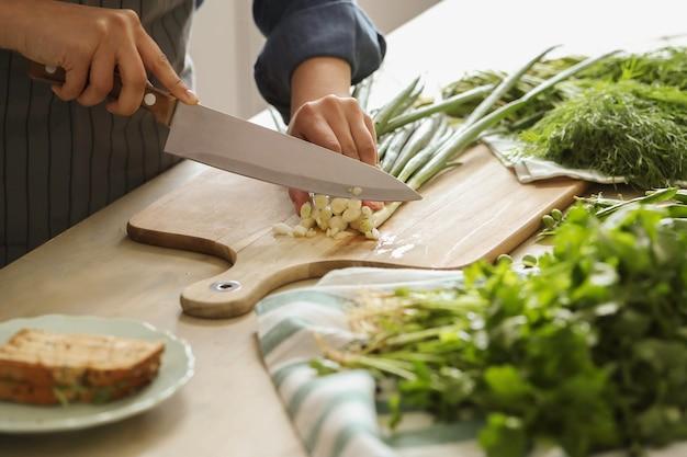 Cocinando. el chef está cortando verduras en la cocina. Foto gratis
