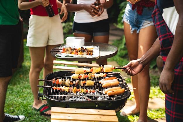 Cocinando para un grupo de amigos a comer barbacoa. Foto Premium