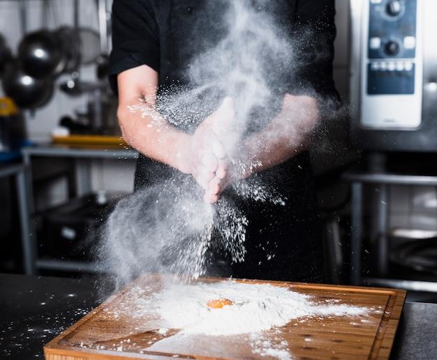 Cocinar aplaudiendo las manos con harina. Foto gratis