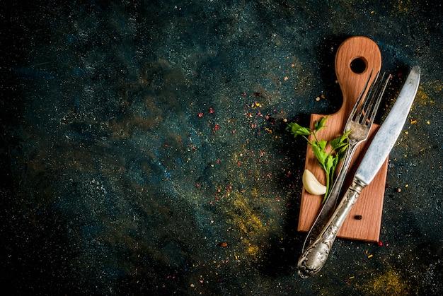 Cocinar el concepto de alimentos, especias, hierbas y aceite para preparar la cena, con tabla de cortar Foto Premium