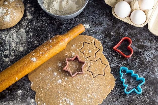 Cocinar galletas de jengibre de navidad con ingredientes sobre un fondo oscuro Foto Premium