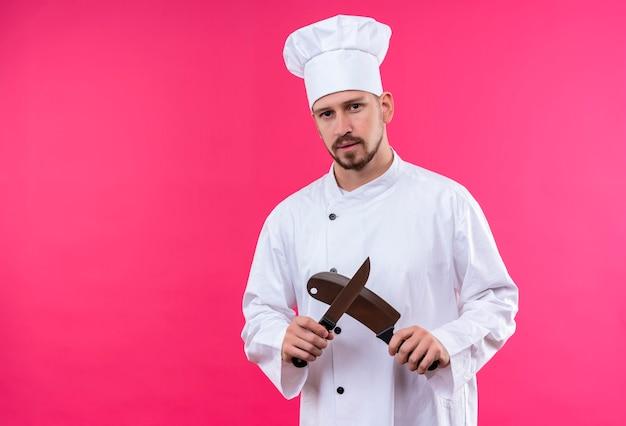 Cocinero de chef masculino profesional en uniforme blanco y sombrero de cocinero sosteniendo cuchillos afilados mirando a cámara con cara seria de pie sobre fondo rosa Foto gratis