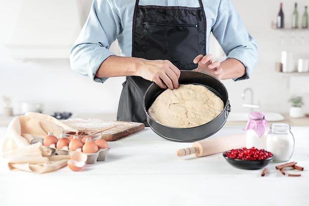 Un cocinero en una cocina rústica. las manos masculinas con ingredientes para cocinar productos de harina o masa, pan, magdalenas, pastel, pastel, pizza Foto gratis