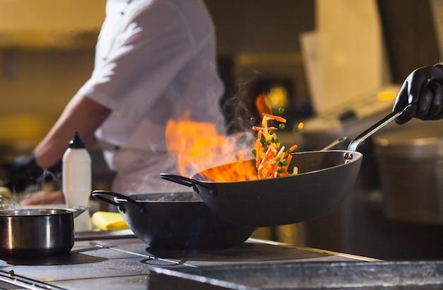 Cocinero haciendo la cena en la cocina del restaurante de alta gama. Foto Premium
