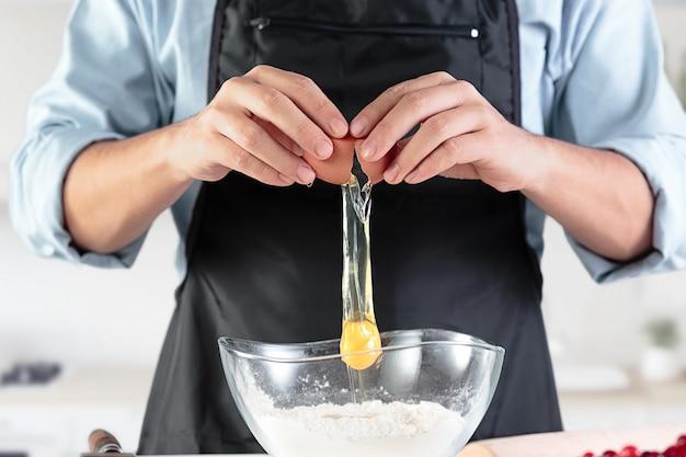 Un cocinero con huevos en una cocina rústica Foto gratis