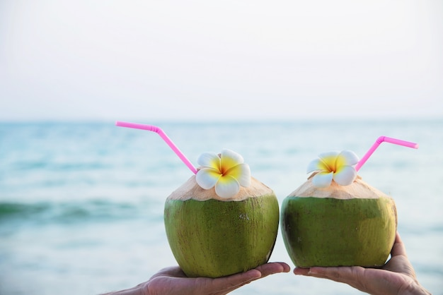 Coco fresco en manos de los pares con plumeria adornado en la playa con la onda del mar - turista de los pares de la luna de miel con concepto de las vacaciones del sol de la fruta fresca y de la arena de mar Foto gratis
