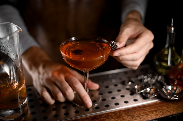Cóctel de alcohol con aceituna dentro Foto Premium