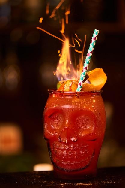 Cóctel alcohólico de zombis que consiste en ajenjo, ron con especias casero, arándano y jugo de toronja en un vaso con forma de calavera Foto Premium