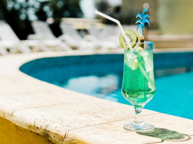 Cóctel azul frío con kiwi y hielo junto a la piscina Foto gratis
