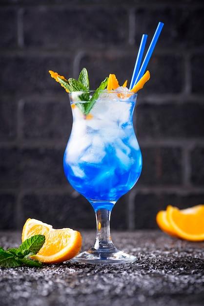 Cóctel azul con hielo y naranja. Foto Premium