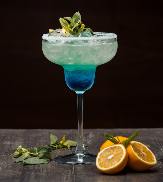 Cóctel azul y verde adornado con limón y menta en vaso de tallo largo Foto gratis