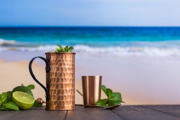 Cóctel frío moscow mules con cerveza de jengibre, vodka y lima sobre fondo de playa y mar Foto Premium