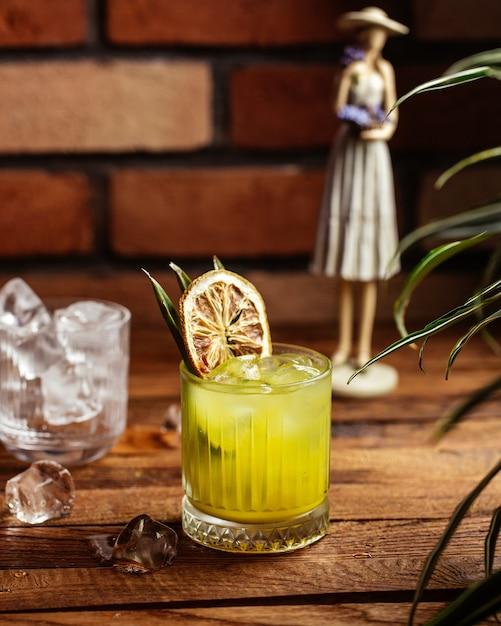 Un cóctel de frutas de vista frontal con cubitos de hielo en el escritorio de madera marrón cóctel jugo de bebida de frutas Foto gratis