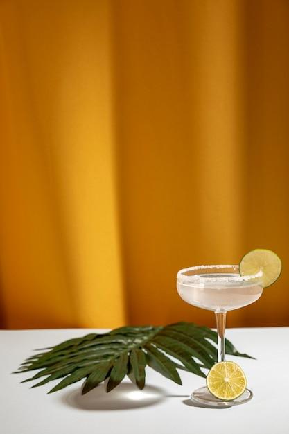 Cóctel margarita con limas en rodajas y hojas de palma en la mesa blanca cerca de la cortina amarilla Foto gratis