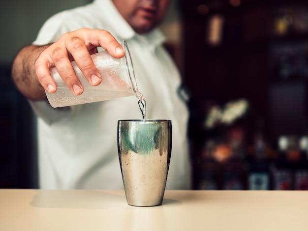 Coctel de mezcla del camarero de sexo masculino en coctelera Foto gratis