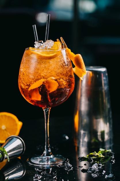 Cóctel de naranja dentro de vidrio con cubitos de hielo picado y tuberías. Foto gratis