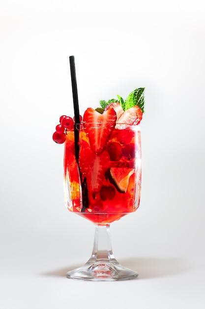 Cóctel refrescante rojo con guarnición de bayas, lima y menta Foto Premium