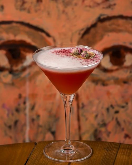 Cóctel rojo espumoso adornado con capullos de rosa secos Foto gratis