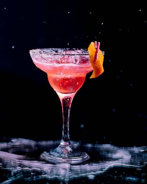 Cóctel rojo con piel de naranja pelada y cubitos de hielo picados. Foto gratis