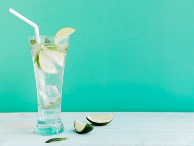 Cóctel transparente con lima, menta y hielo en estudio. Foto gratis