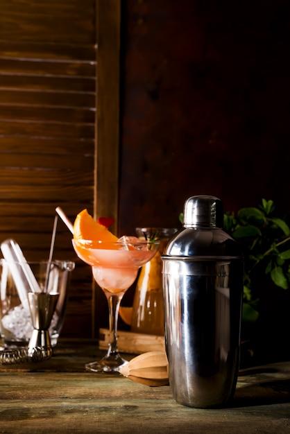 Coctelera, licor, pinzas y cuchara con hielo en un cubo para preparar un cóctel de verano Foto Premium