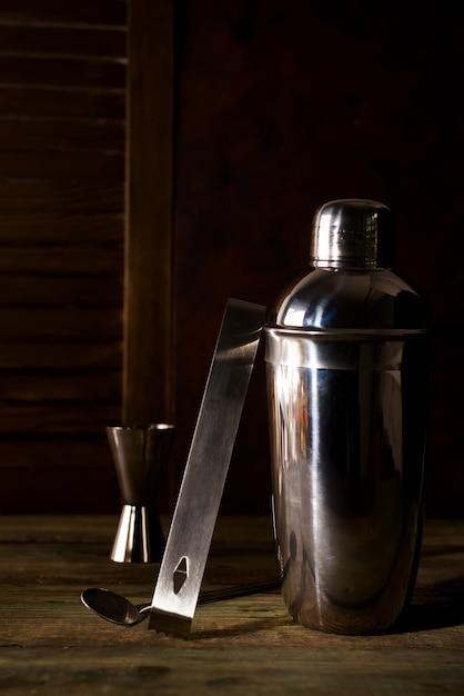 Coctelera, licor, pinzas y cuchara con hielo en un cubo Foto Premium