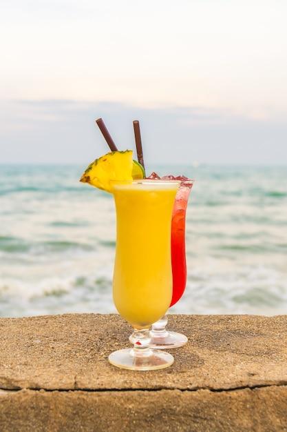 Cócteles helados bebiendo vaso con mar y playa Foto gratis
