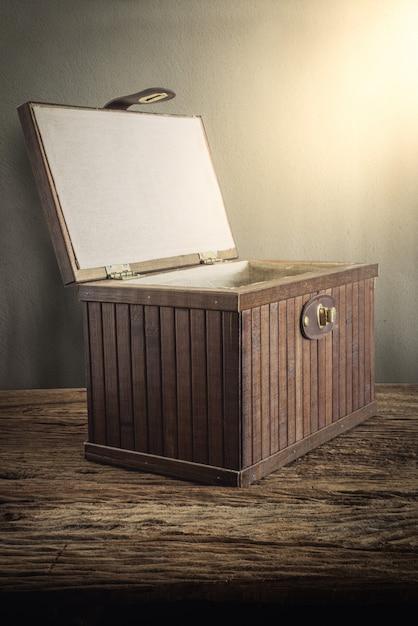 Cofre de madera viejo con abierto iluminado en tablero de madera contra pared grunge Foto Premium