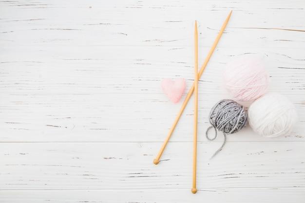Cojín rosa en forma de corazón; ganchillo y bola de hilos en el fondo de madera Foto Premium