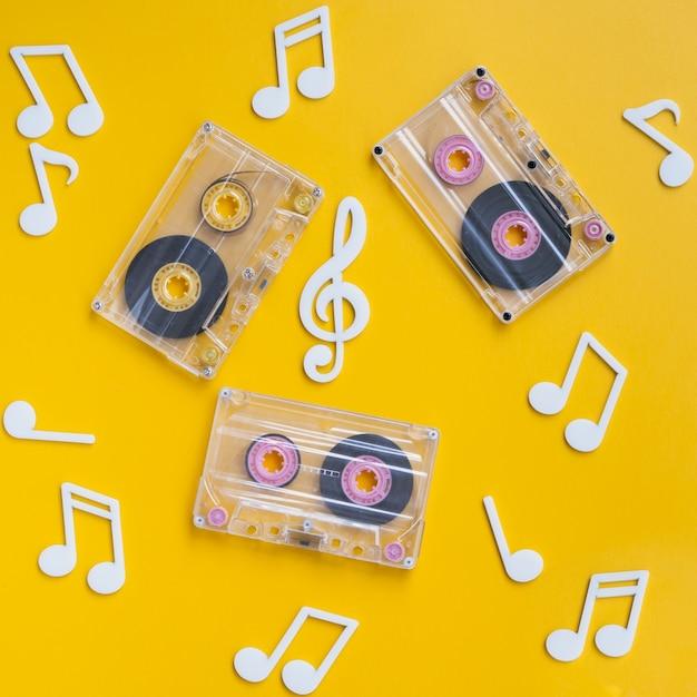 Colección de cintas de cassette transparentes con notas musicales alrededor Foto gratis