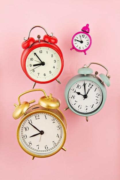Colección de despertadores coloridos brillantes sobre el fondo rosa Foto Premium