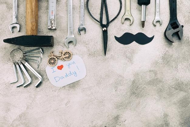 Colección de instrumentos cerca de bigote decorativo con palabras i love you daddy Foto gratis