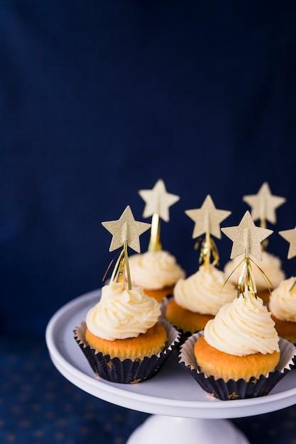 Colección de sabrosos pasteles con crema de mantequilla y estrellas en el stand. Foto gratis