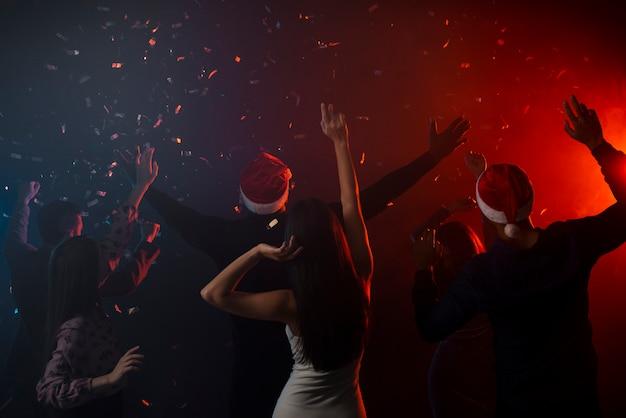 Colegas bailando en confeti en la fiesta de año nuevo Foto gratis