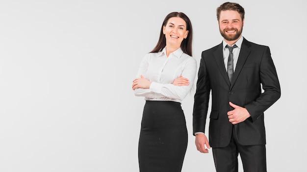 Colegas mujer y hombre sonriendo y de pie juntos. Foto gratis