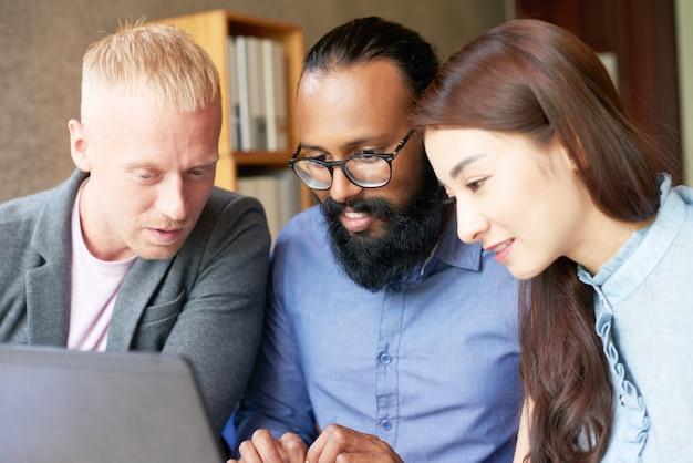 Colegas multiétnicos trabajando juntos en la computadora portátil en la oficina y mirando la pantalla Foto gratis