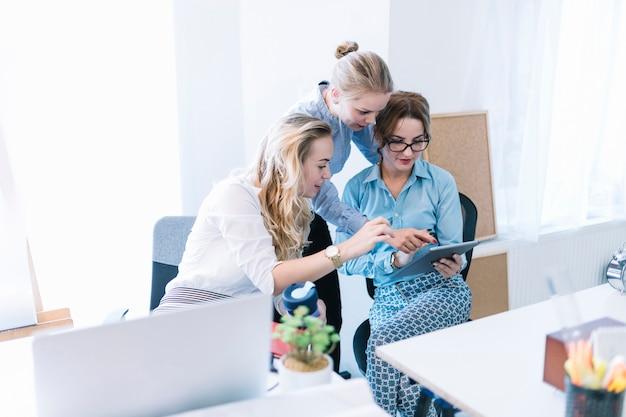 Colegas de sexo femenino que señalan y que miran la tableta digital en la oficina Foto gratis