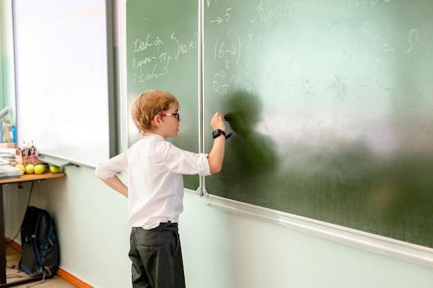 Colegial caucásico haciendo ejercicio en la pizarra en el aula. Foto Premium
