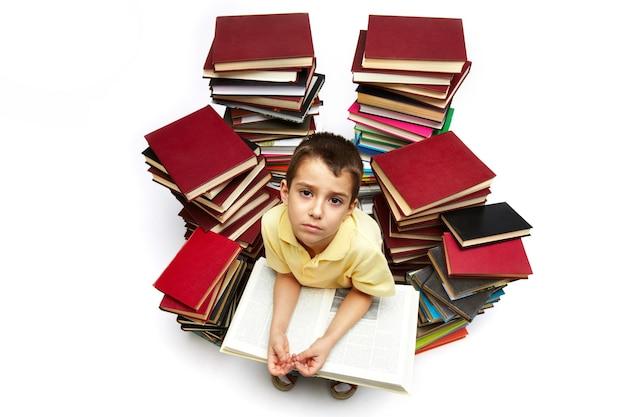 Colegial leyendo rodeado de libros Foto gratis