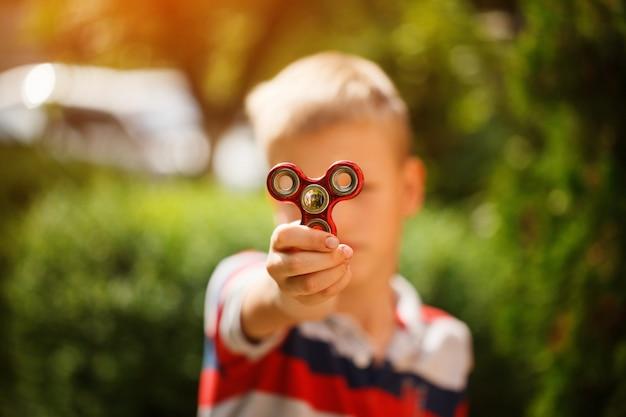 El colegial sostiene una inquietud del hilandero en sus manos. juguete de moda y popular para niños y adultos. Foto Premium
