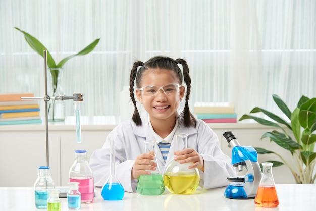 Colegiala asiática con trenzas sentado en el escritorio con microscopio y viales con líquidos coloridos Foto gratis