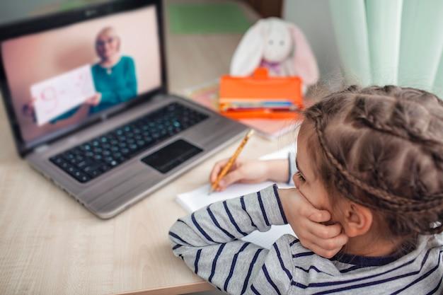 Colegiala bastante elegante que estudia matemáticas durante su lección en línea en casa, autoaislamiento Foto Premium