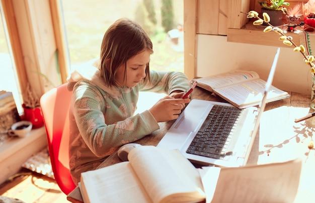 La colegiala hace la tarea en casa y escribe un mensaje en su teléfono móvil Foto gratis