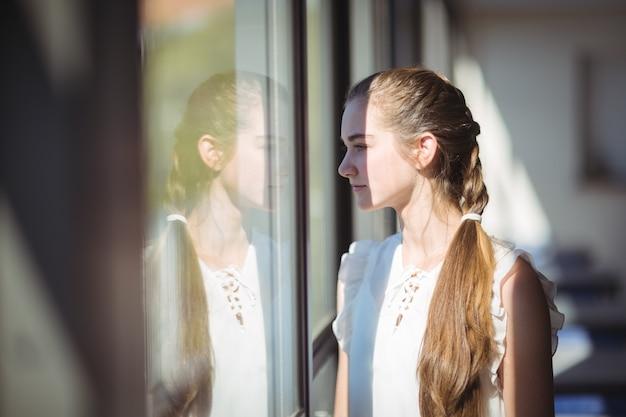 Colegiala mirando por la ventana en el aula Foto Premium