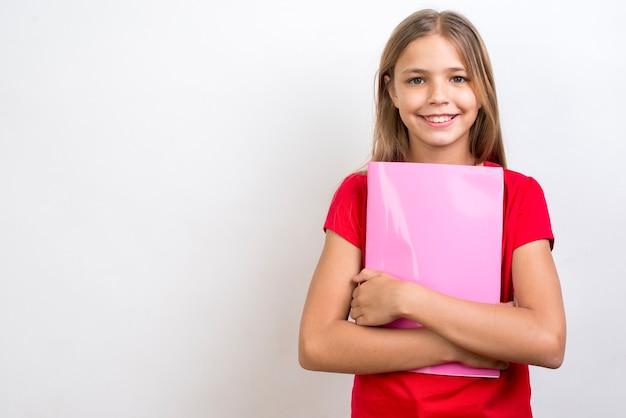 Colegiala sonriente llevando cuaderno Foto gratis