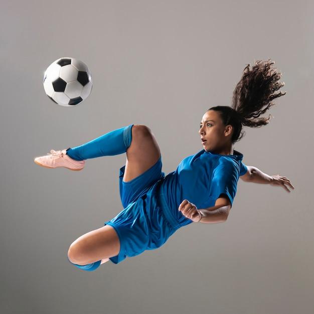 Coloca el fútbol en ropa deportiva haciendo trucos Foto gratis