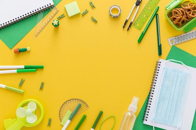 Colocación plana de materiales de regreso a la escuela con cuaderno y mascarilla Foto gratis