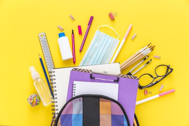 Colocación plana de materiales de regreso a la escuela con mochila y gafas Foto Premium
