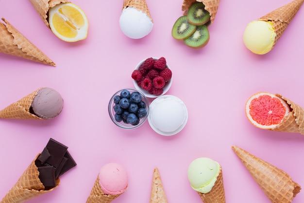 Colocación superior de sabores de helados con fondo rosa Foto gratis