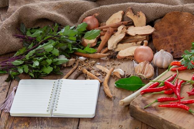 Se colocan varios ingredientes utilizados para hacer comida asiática junto con los cuadernos en la mesa de madera. Foto gratis